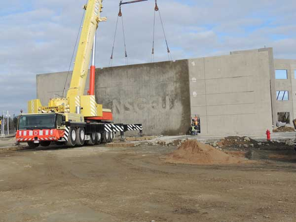 A crane lifts the wall into place
